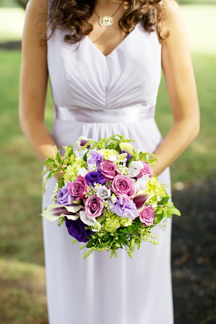 Bridesmaids carried round bouquets of purple and cream flowers and lush greenery.