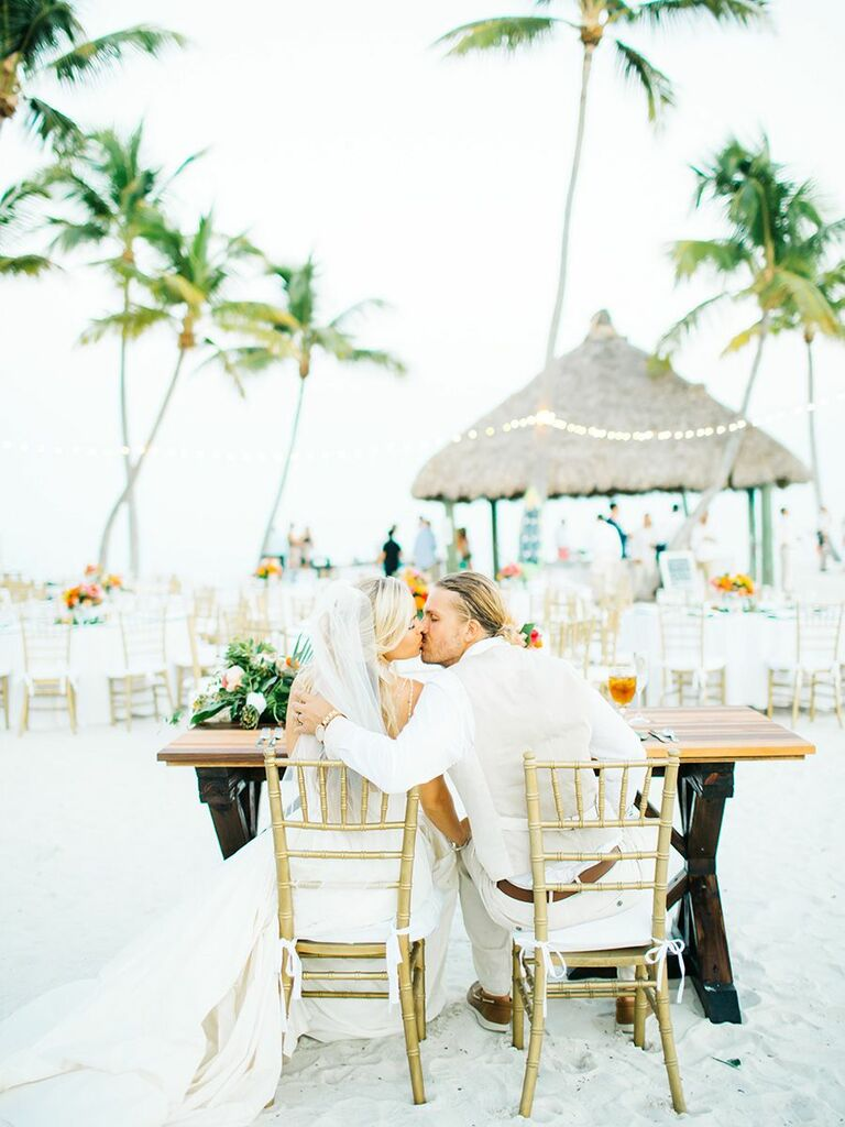 bride and groom kissing on the beach beach reception