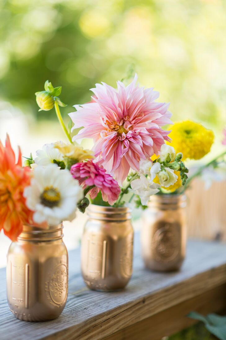 The centerpieces at the 1850 House Inn in Rosendale, New York, were a true labor of love. Samantha's bridal party painted mason jars gold for the occasion and filled with them with bright dahlias, poppies, snapdragons, zinnias and marigolds the morning of the wedding.