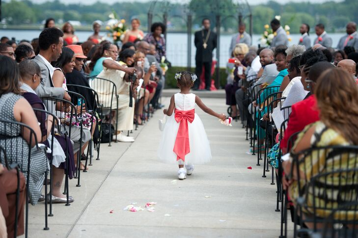 Ebony and Jeremy's flower girl walked down the aisle in a sweet white dress with a full tulle skirt and bold coral sash fastened into a bow. Her pink and white flower petals were also the main aisle decor.