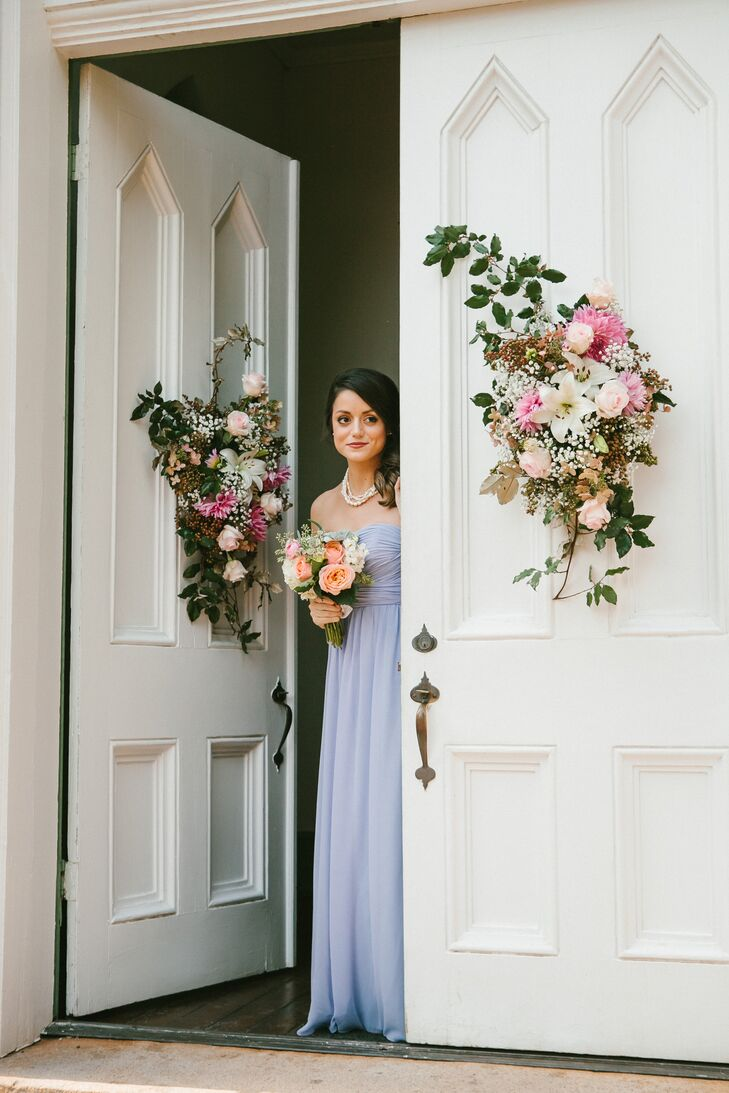 Sarah's bridesmaids wore strapless, floor length dresses in lavender to her wedding. The church doors were decorated with flower arrangements of peonies, lilies, roses and baby's breath for Sarah and Jonathan's wedding.