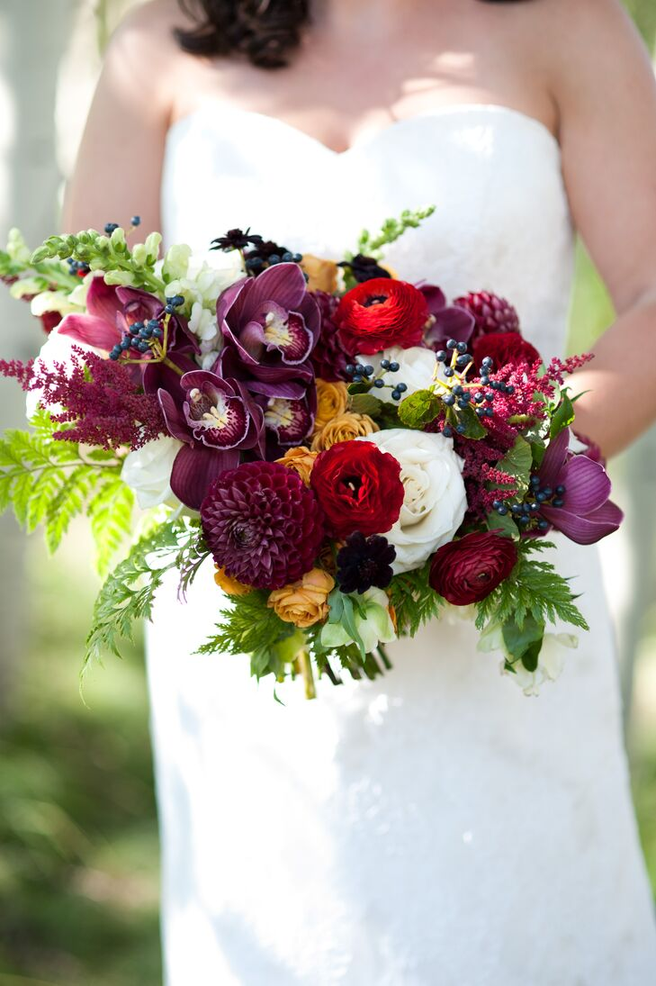 Tara carried orchids, dahlias, ranunculuses, roses and berries in her lush burgundy, red and orange bouquet.