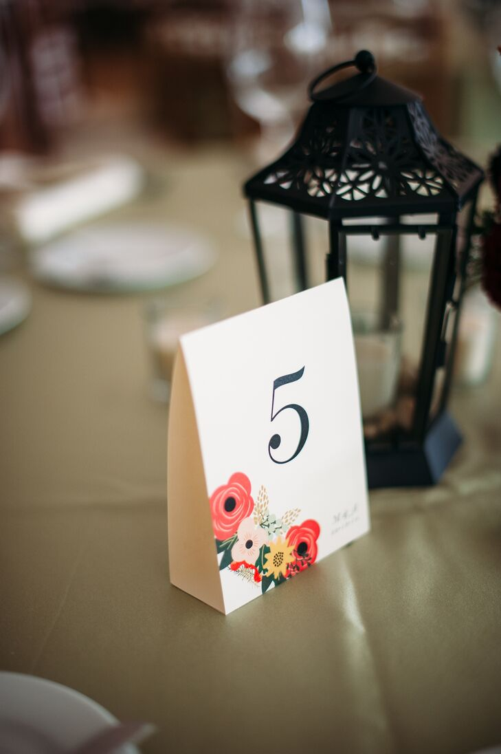 White simple table numbers had colorful floral graphics printed on the corner. They were designed by a family friend of the bride and the groom.