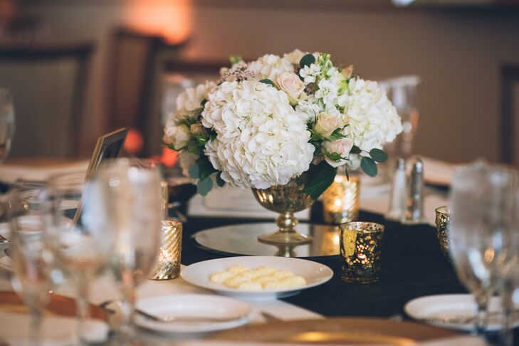 Some of their reception tables also featured low, garden-style arrangements. White hydrangeas, blush garden roses, seeded eucalyptus and scabiosa pods flowed along the sides of its gold pedestal vase. A mirror base elevated the design. Gold votive candles also surrounded the arrangement.