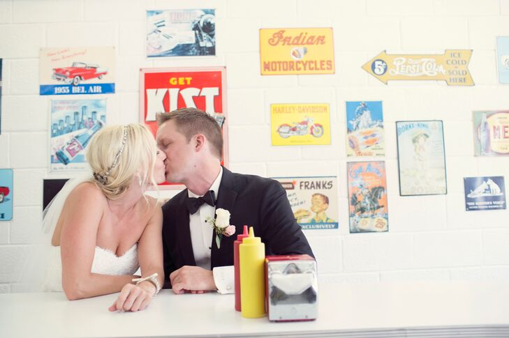 Bride and Groom Kiss at Diner Table with Vintage Signs