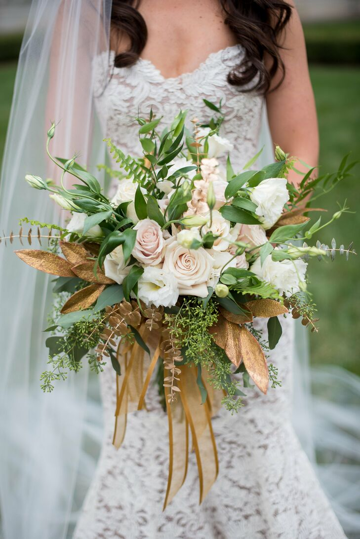 "Sarah knew she wanted big ivory roses in her bouquet, but couldn't decide whether to add a colored flower for visual interest. In the end, she decided against it. ""My florist helped by spray-painting and adding gold greenery to the bouquet to give it something special,"" she says."