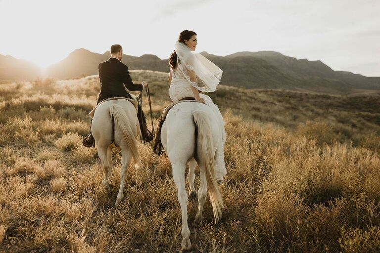 Couple riding away on horse during sunset