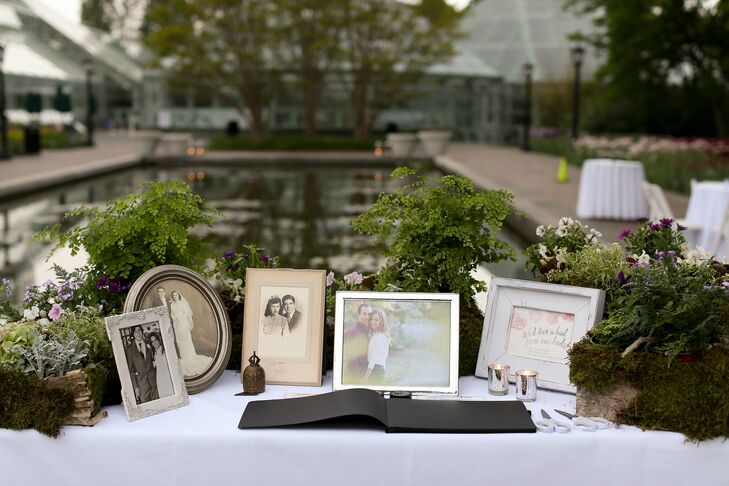 "To pay tribute to their family heritage, Lauren and Will decorated their guest book table with framed photos of their parents, grandparents and other relatives on their own wedding days. Wildflowers and ferns were sprinkled throughout, adding to the display's garden-inspired aesthetic, while offering a way for guests to express their well-wishes for the newlyweds. ""Guests could cut them as they liked and paste them into the book alongside their message,""  Lauren says."