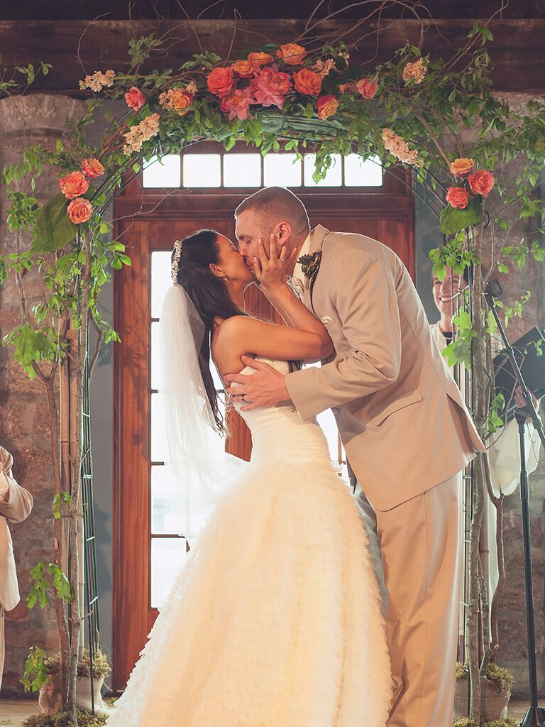 A simple vintage exposed wood wedding arch with flower and greenery garland