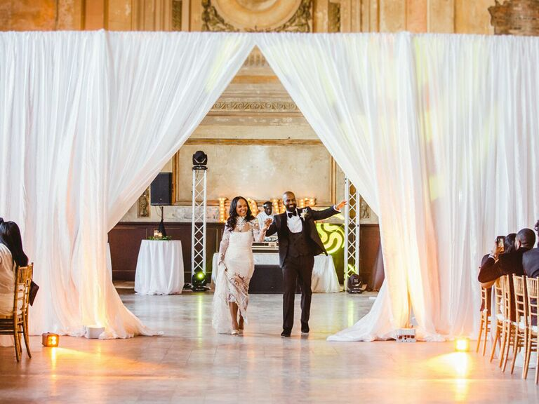 Bride and groom glam wedding reception entrance with draped curtain backdrop