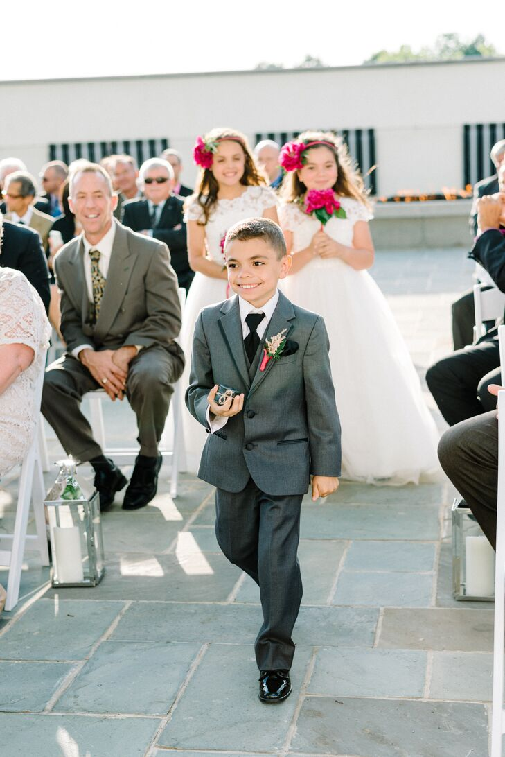 Their ring bearer's look matched each groomsmen to a T. Like the rest of their wedding party, he wore a charcoal gray tuxedo from Men's Wearhouse with a formal black tie, black dress shoes and matching pocket square. His pink astilbe boutonniere brought a hint of color and vintage style to the outfit.