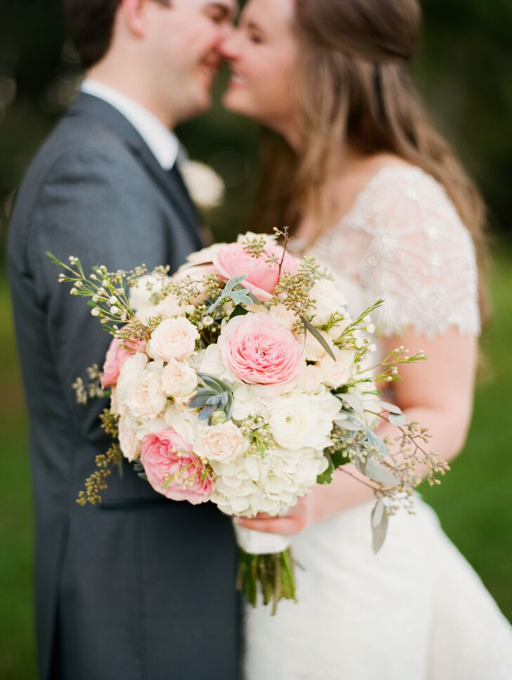 Kaitlin's bridal bouquet featured pink garden roses, white ranunculus, succulents, wax flower, dusty miller, seeded eucalyptus, and white hydrangeas.
