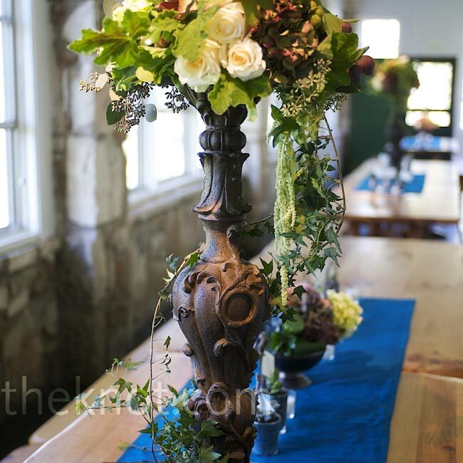 Antique-finished candle stands filled with peonies, hydrangeas, mums, ranunculus, anemones, and roses, and peacock blue runners decorated the dining tables.