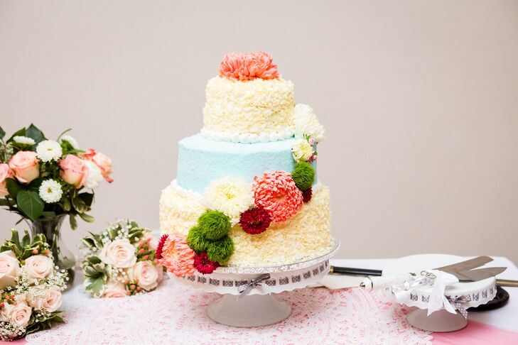 The wedding cake was iced with blue and yellow frosting, and then decorated with dahlia, chrysanthemum and moss balls. The cake was positioned on a stand ned to the serving set.