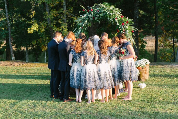 During the ceremony, a prayer circle was held with the bridal party in front of an arch of greens and small red and white florals.