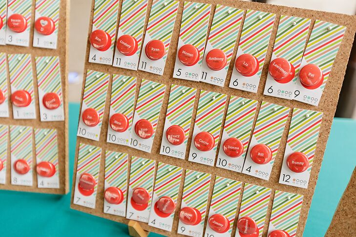 Escort cards were hung on a board for guests to find their table number, designed in red, green and neutral hues with a bright red pin.
