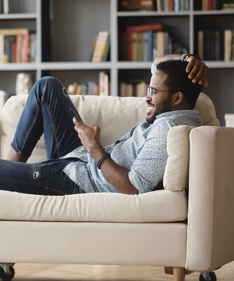Man lounging on sofa wearing LensDirect glasses and smiling at his phone