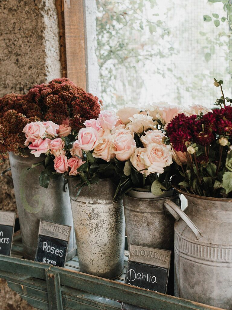 European-inspired metal buckets with fresh roses and delphiniums as wedding decor