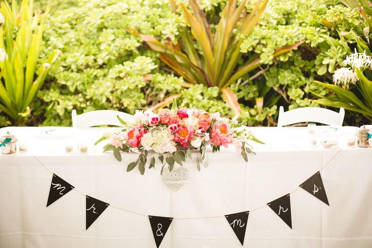 """Veronica and Tim sat at the sweetheart table covered in white linens, with a """"Mr. & Mrs."""" black flag sign draped across the front. A white and pink blossoming centerpiece decorated the middle of the table."""