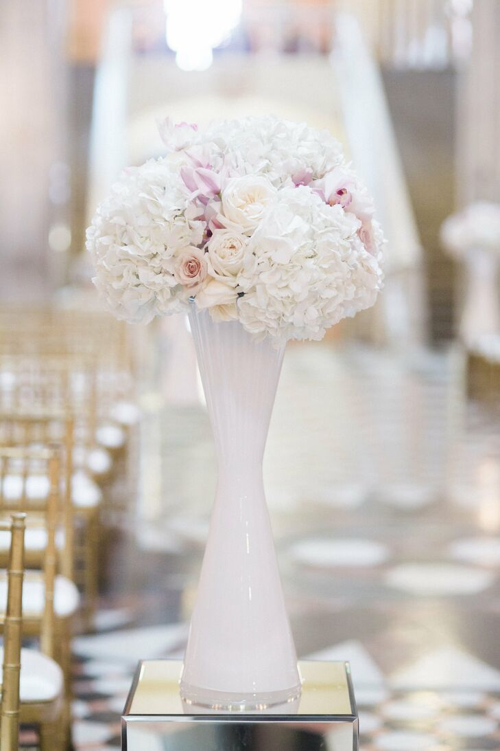 A lush arrangement of hydrangeas, dahlias, orchids, garden roses, roses and peonies with a marbling effect in tall, cinched white vases rested atop mirrored pedestals in varying heights along each side of the aisle.