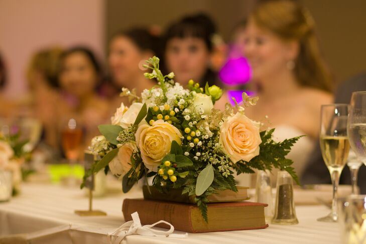 Centerpieces at the reception were made up of roses and hypericum berries on stacks of hardcover books for a vintage touch.