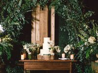 Three-tier rustic wedding cake on tree stump stand under greenery arch