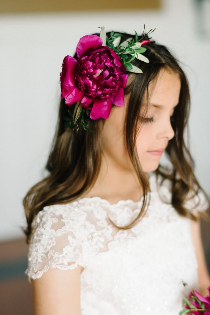 Both Sarah and Steve's flower girls stood out during the wedding with dramatic accessories. Their cousins each carried a mini raspberry peony bouquet and wore the same accent in her flower crown. Surrounded by greenery and eucalyptus, the color popped against their white lace dresses.