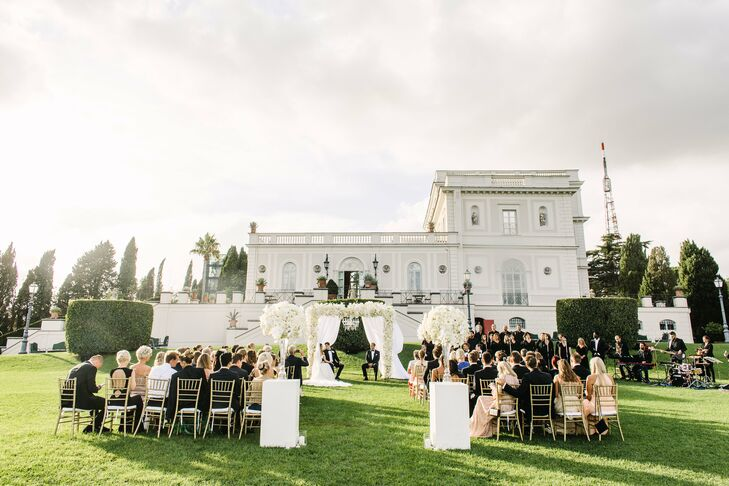 """The ceremony unfolded outdoors in Villa Miani's beautifully manicured English garden. """"We have always wanted a ceremony outside, and this spot fit us perfectly,"""" Silje says. """"To complement the gorgeous white villa, we wanted all the flowers to be white and the rest of the decor to be gold."""""""