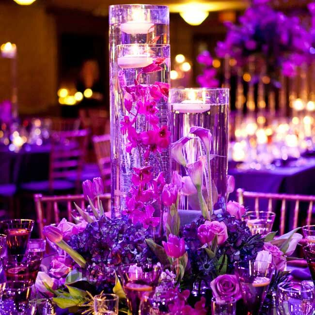 Tall cylinders filled with submerged tulips, roses and orchids were set in a bed of purple flowers and greens.