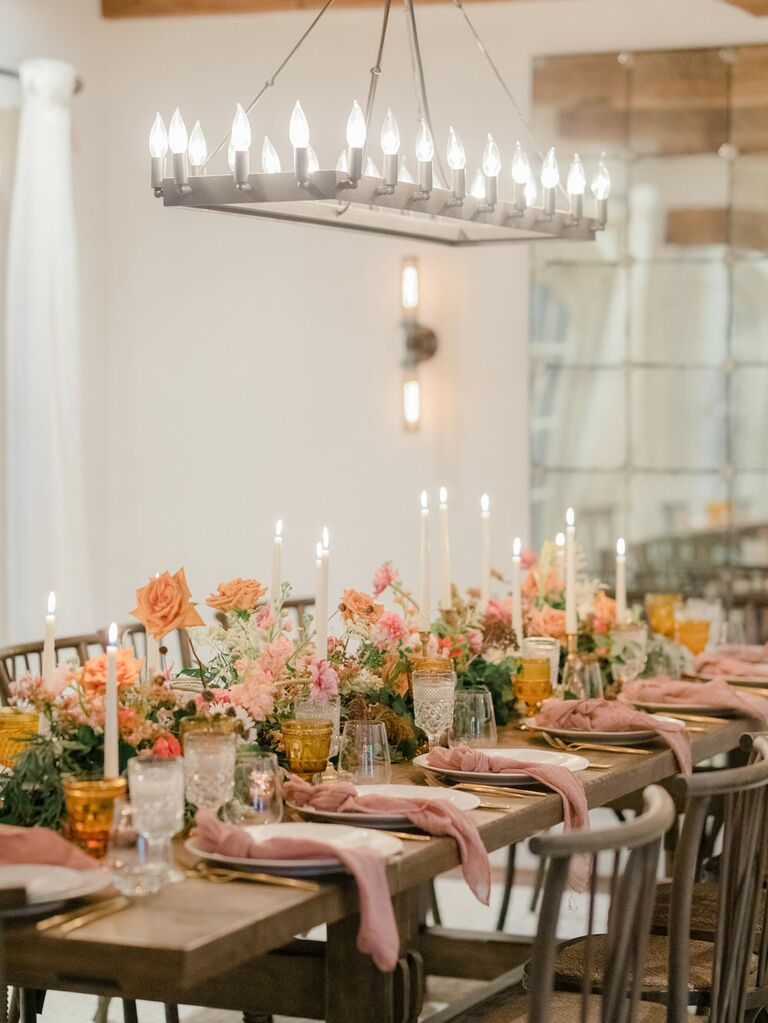 Muted pink and orange flowers and table linens at summer wedding