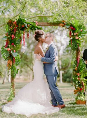 First Kiss Under Wedding Arch Covered in Tropical Leaves