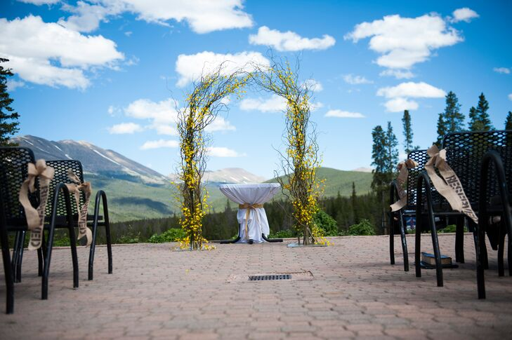 Jessica and Phil exchanged vows under a branch and yellow flower wedding arbor overlooking swoon-worthy views of the mountains.
