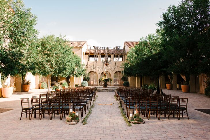 "The ceremony took place outside on the courtyard at Serra Plaza in San Juan Capistrano, California, with rows of wooden chiavari chairs creating an aisle leading up the altar. ""We got married in front of a beautiful fountain, decorated with gorgeous lush peach and coral flowers that spilled over the edge,"" Stacy says. ""Market lights and chandeliers hung above us and were draped with dripping moss. It was truly a romantic setting for a ceremony."""