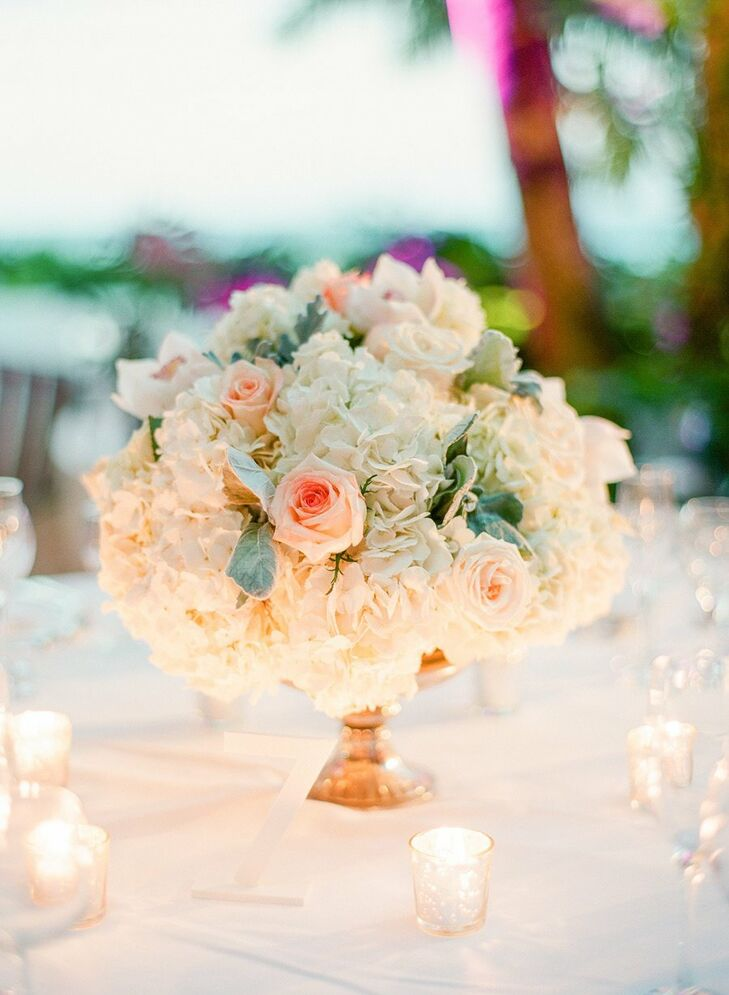 Blush and ivory blooms—including roses and hydrangeas—with hints of green created a romantic look while maintaining the neutral color palette.