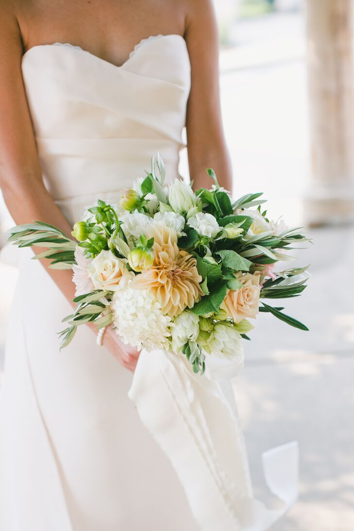 With a garden-inspired theme pervading the day, a bridal bouquet with lots of texture and full blooms was a must for Jessica's walk down the aisle. Tesoro Flowers created a dramatic, hand-tied bouquet bursting with dahlias, hydrangeas, roses, olive leaves and more in peach, ivory and green hues that corresponded perfectly with the day's palette.