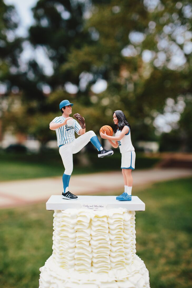 """""""Our wedding cake topper was personalized to look like us and was made to look like an action shot from our sports in our athletic jerseys,"""" says the couple."""