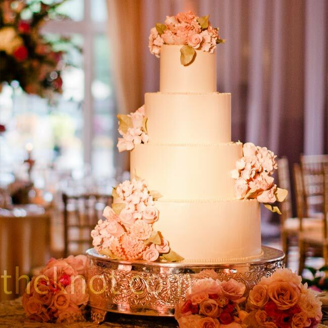 Coated in buttercream frosting, the four-tiered cake was decorated with handmade sugar flowers.