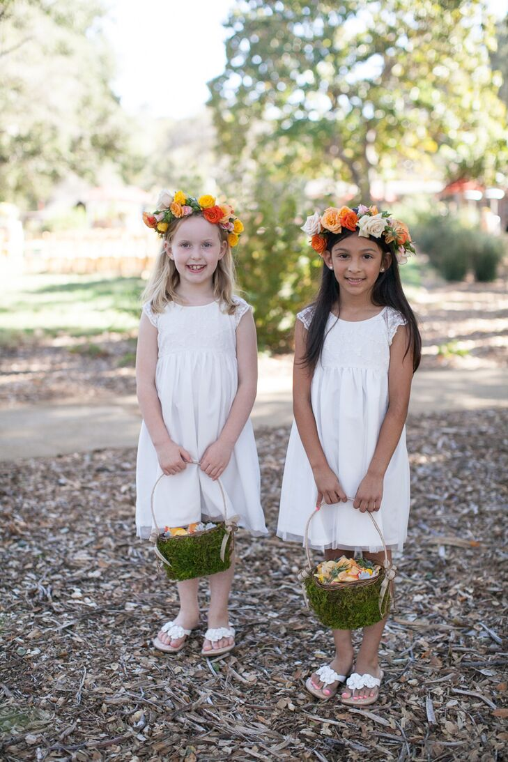 Flower girls wore simple knee-length white dresses and white flip-flops with fabric flowers on the top. The two girls wore matching colorful flower crowns arranged with a variety of roses, and held moss-covered baskets filled with rose petals for the ceremony.