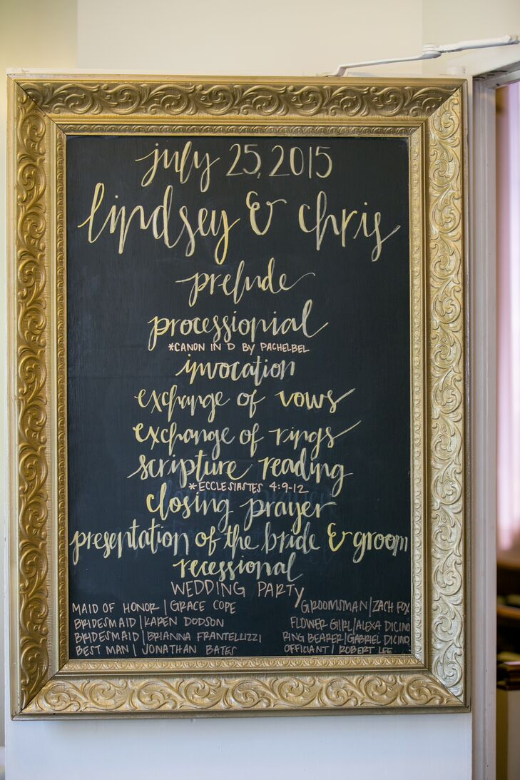An elegant gold-framed chalkboard displayed the wedding program for all guests to see, showcasing everything from the series of ceremonial events to the wedding party members.