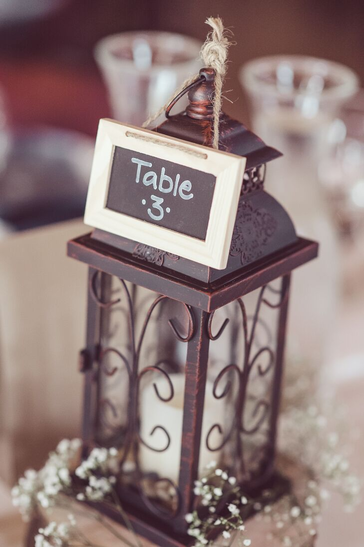 Centerpieces were created using lanterns on a wood slab and chalkboard table numbers.