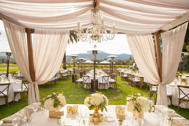 In keeping with the day's chic aesthetic, white linens were used to create cabanas at the outdoor reception at Chateau St. Jean Winery in Kenwood, California. Chandeliers added an extra touch of elegance.