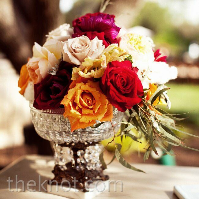 Small vases filled with multicolored roses added brightness to the sign-in table.