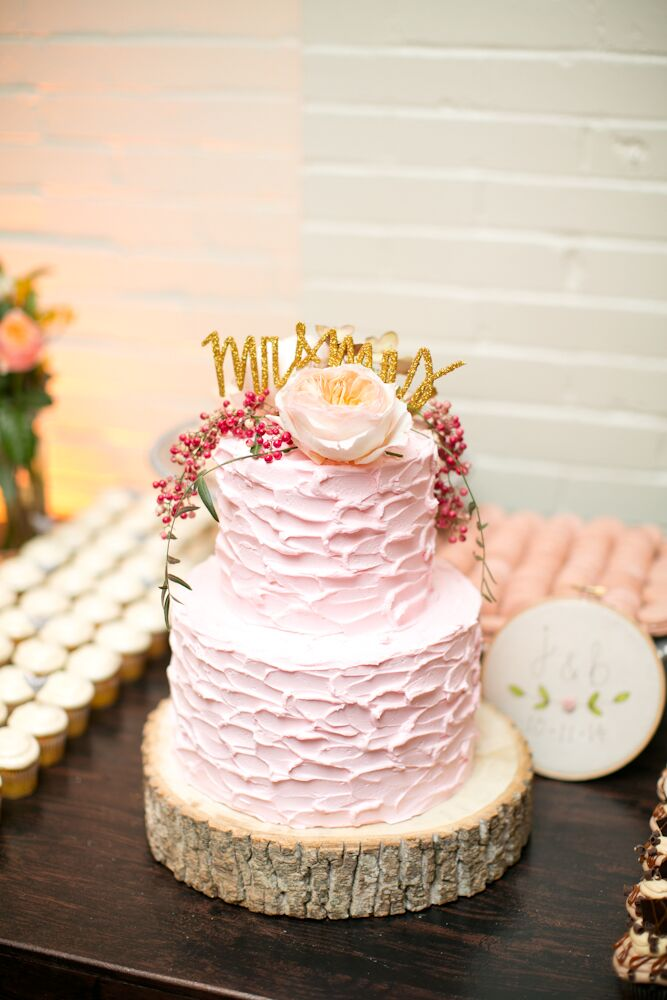 """""""I loved my wedding cake,"""" Jessica says. """"I knew I wanted to do something different from your traditional wedding cake—why not have fun with it?—and went with a blush pink textured icing, adding garden roses and berries to the top. I bought a topper on Etsy that read 'Mr. and Mrs.' in gold—a perfect touch."""""""