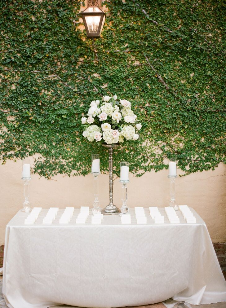 The escort cards were elegantly displayed alongside pillar candles and a pewter candelabra topped with blush and ivory flowers.