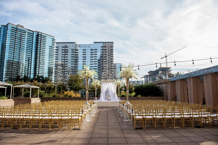 Dramatic floral arrangements in tall vases were placed at the beginning and end of the aisle, and the bride and groom were married under an arbor draped in ethereal fabric and flowers.