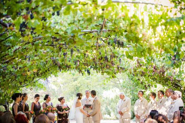 Gia and James exchanged vows under a romantic canopy of grapevines.