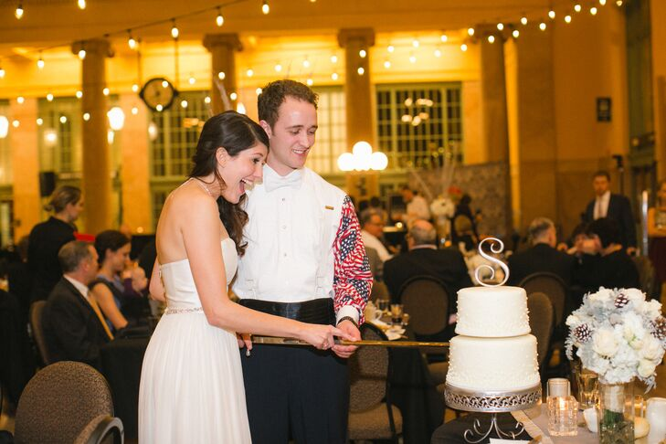 Though Amy and Matthew decided to serve milopita, a dessert of apple slices, cream cheese and ricotta baked in phyllo dough and topped with honey cinnamon syrup, for dessert instead of cake, they had a small cake made for the traditional cake cutting. The couple incorporated another military tradition for the cake cutting, using a ceremonial saber to slice the cake.