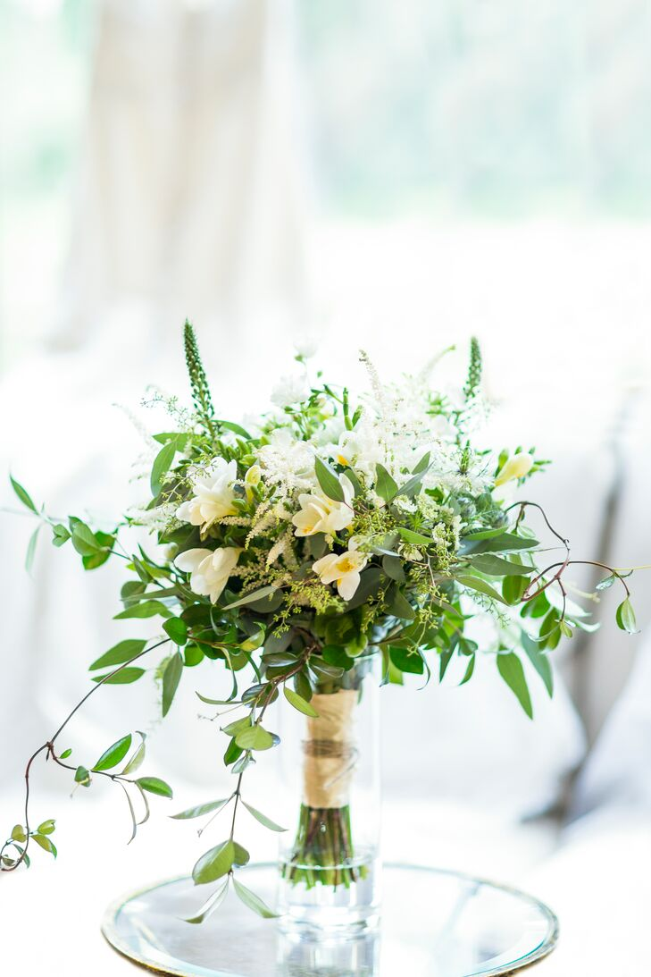 Amy of Amy Harvey Designs created Faith's hand-tied bouquet with overflowing greens and white flowers, including freesia and veronica. The undone look fit her natural wedding style.