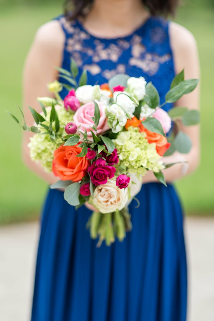 Bridesmaid bouquets incorporated vibrant orange and pink roses, which were eye-catching set off by the cobalt bridesmaid gowns.