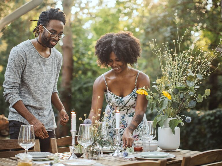 couple setting dinner table outside